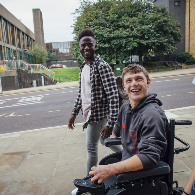 young man in power wheelchair with two friends